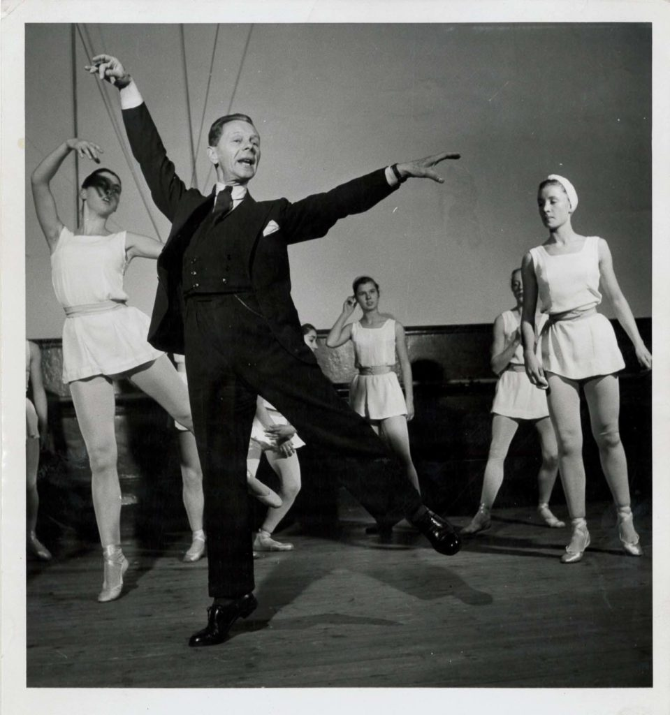 photo of a male dance teacher in a suit showing a move to a group of ballerinas