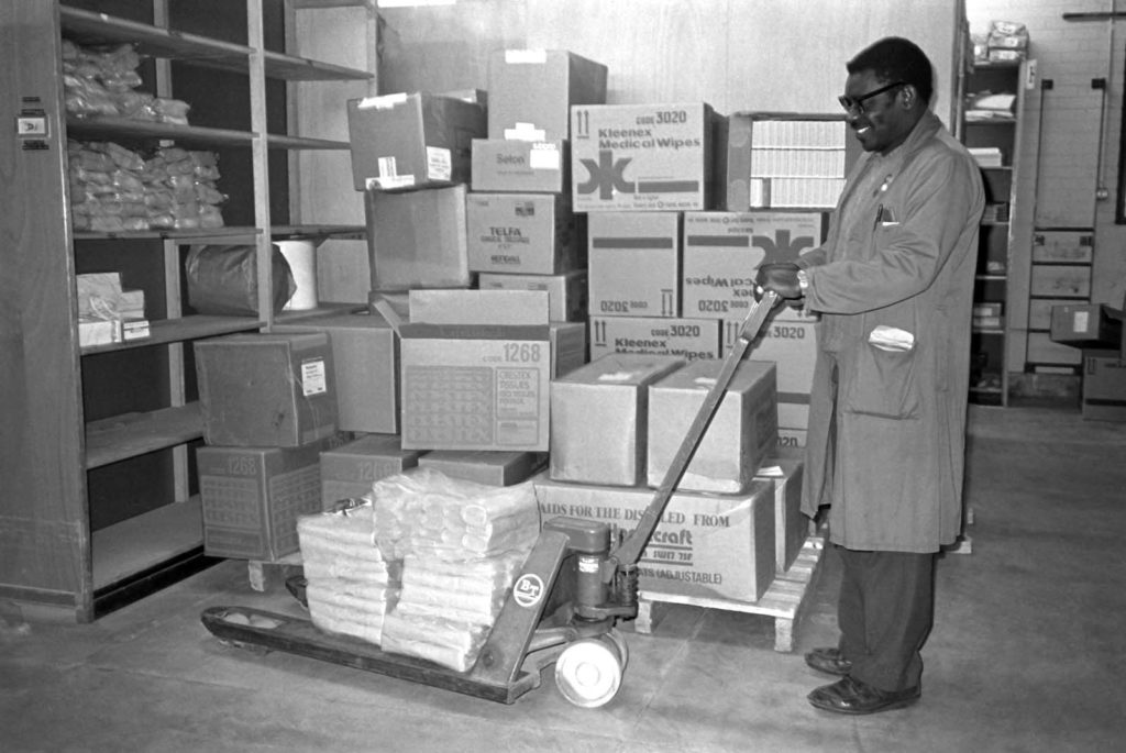 black and white photo of a porter moving boxes
