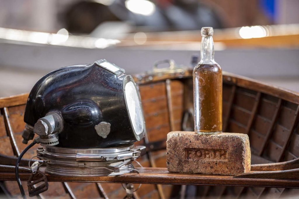 photo of a diving helmet, bottle of whisky and an old brick resting on the seat of a rowing boat