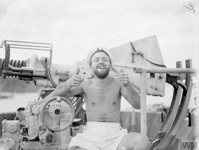 photo of soldier sat on large gun with cigar