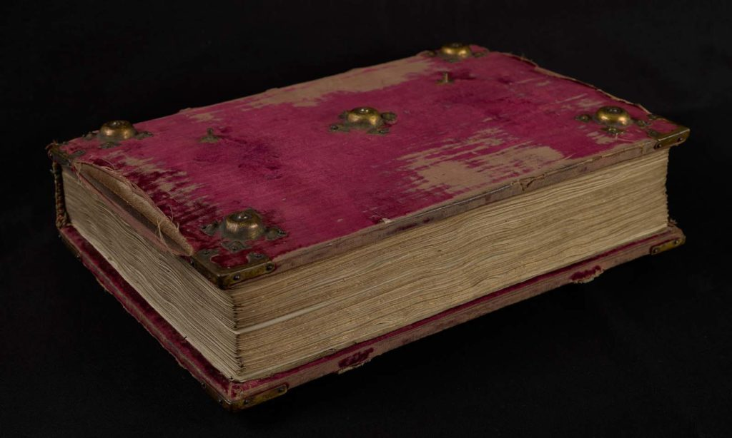 a photo of worn red velvet covered book with raised bosses in the corners and centre