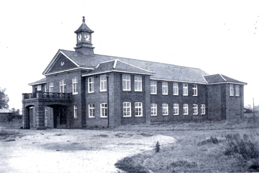 black and white photo of a two storey building with clocktower on top
