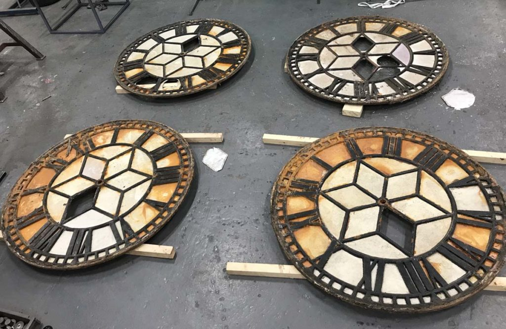 photo of four clock faces with rust