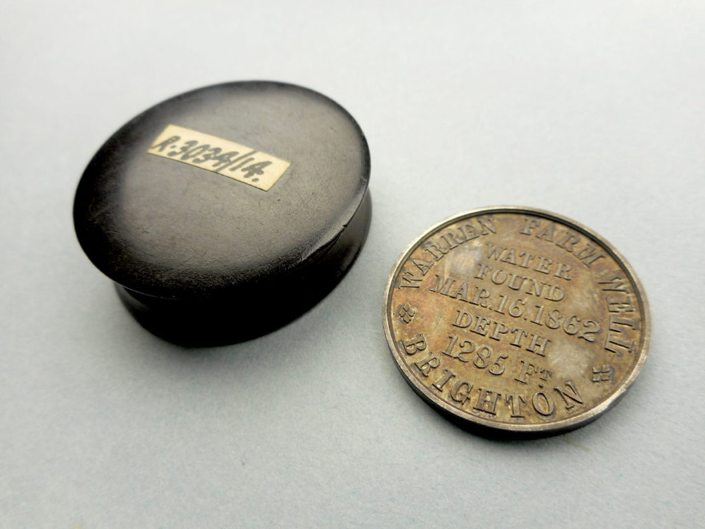commemorative coin reading 'Warren Farm Well Brighton water found Mar.16.1862 depth 1285 ft' pictured next to small circular black case