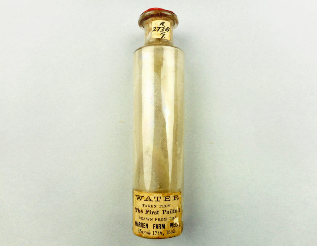glass vial sealed with red wax reading 'water taken from the first pailful drawn from the Warren Farm Well March 17th 1862'