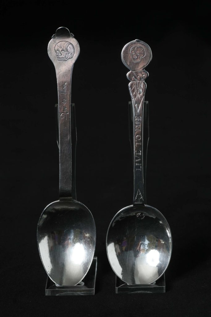 photo of a two silver spoons with deaths heads on their handles