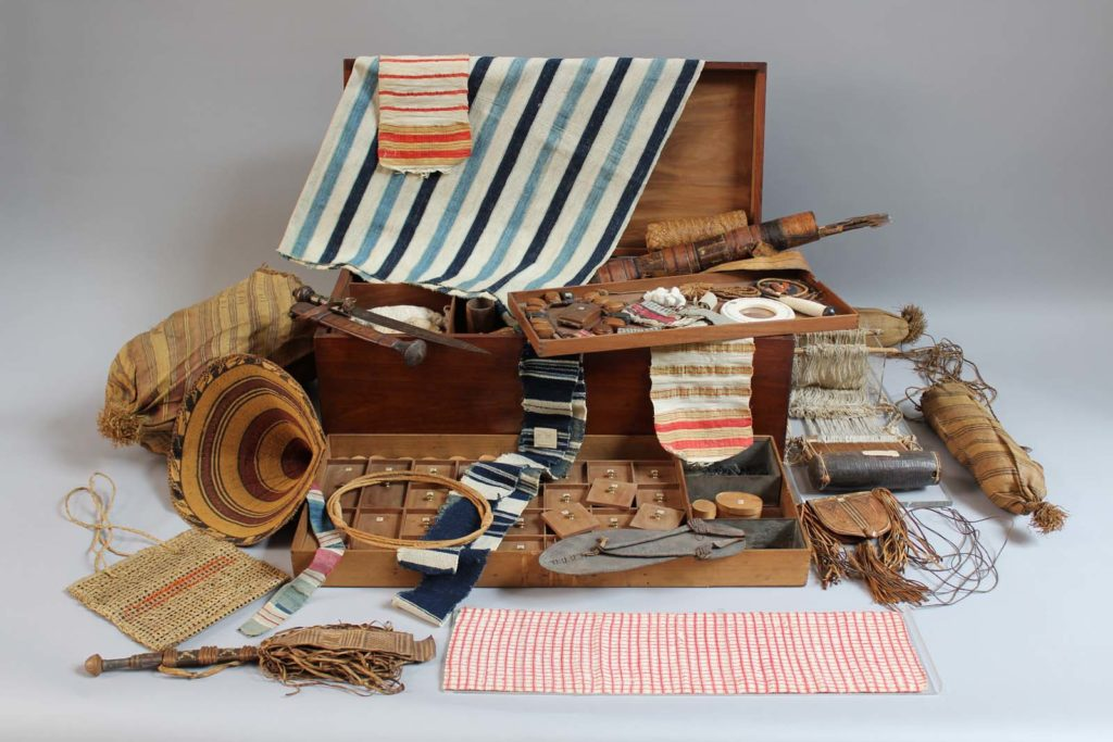 photo of African textiles and other objects displayed around a case