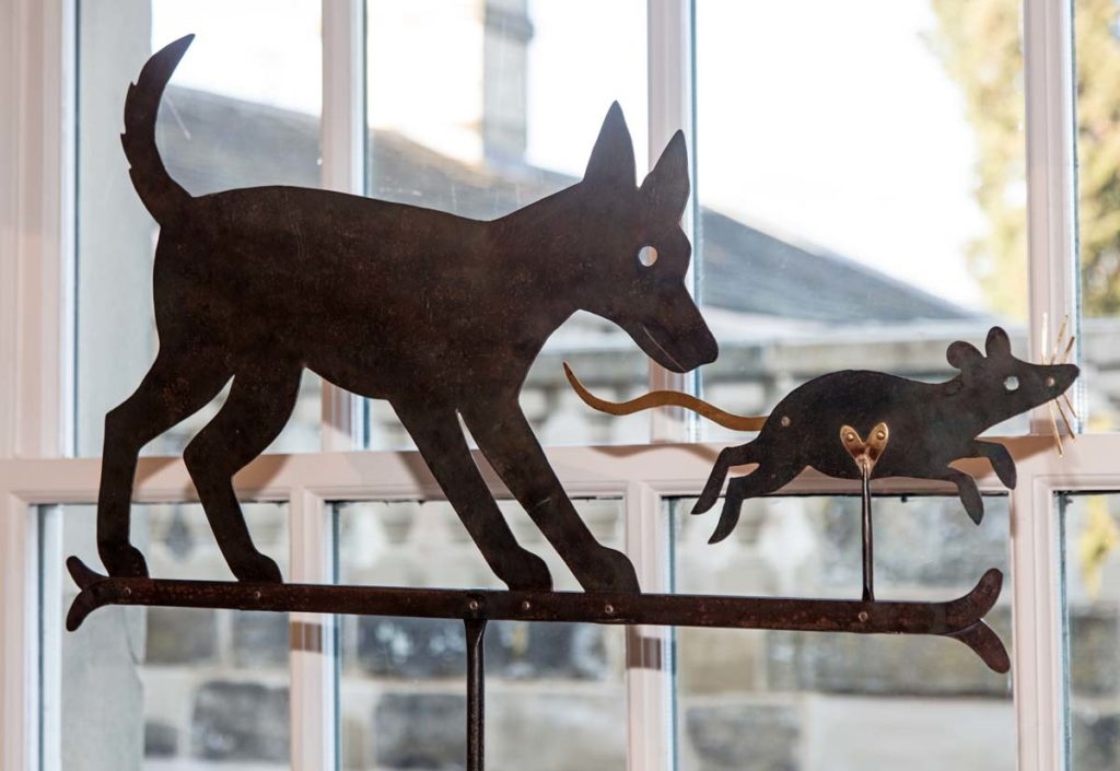 a metal cout out motif of a dog chasing a rat
