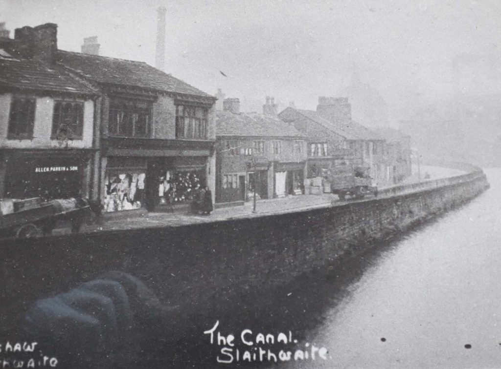 old photo showing a row of shops next to a canal