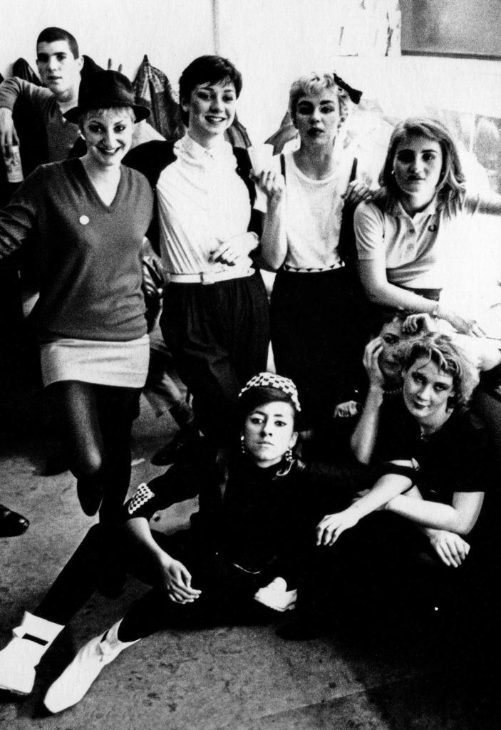 backstage photo of a girl band all dressed in mod and ska clothes
