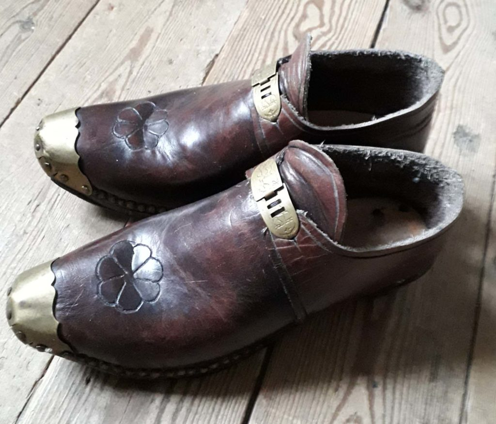 pair of brown clogs with brass clasps and toe ends