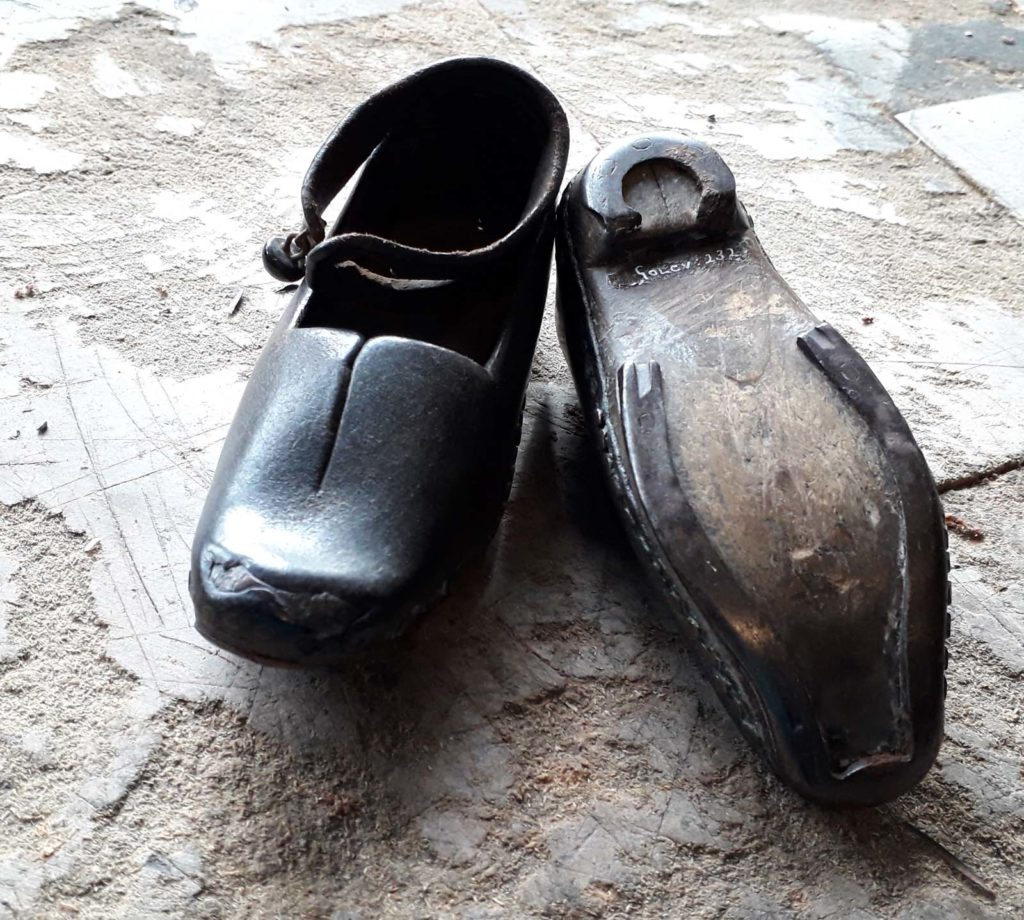 a photo of a pair of wooden soled leather clogs