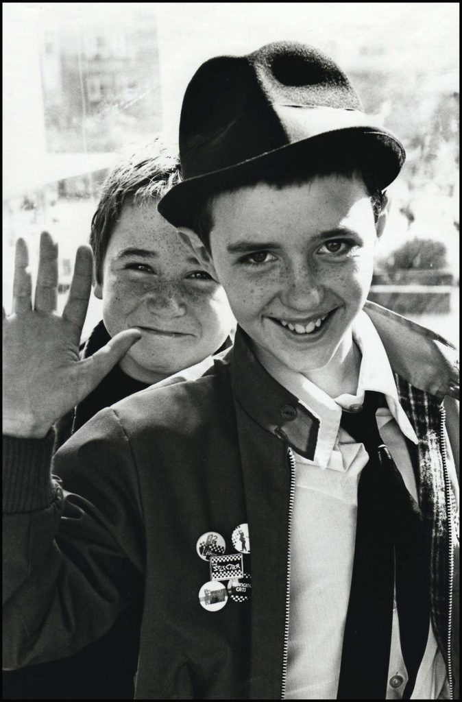 photo of two young ska fans smiling a waving