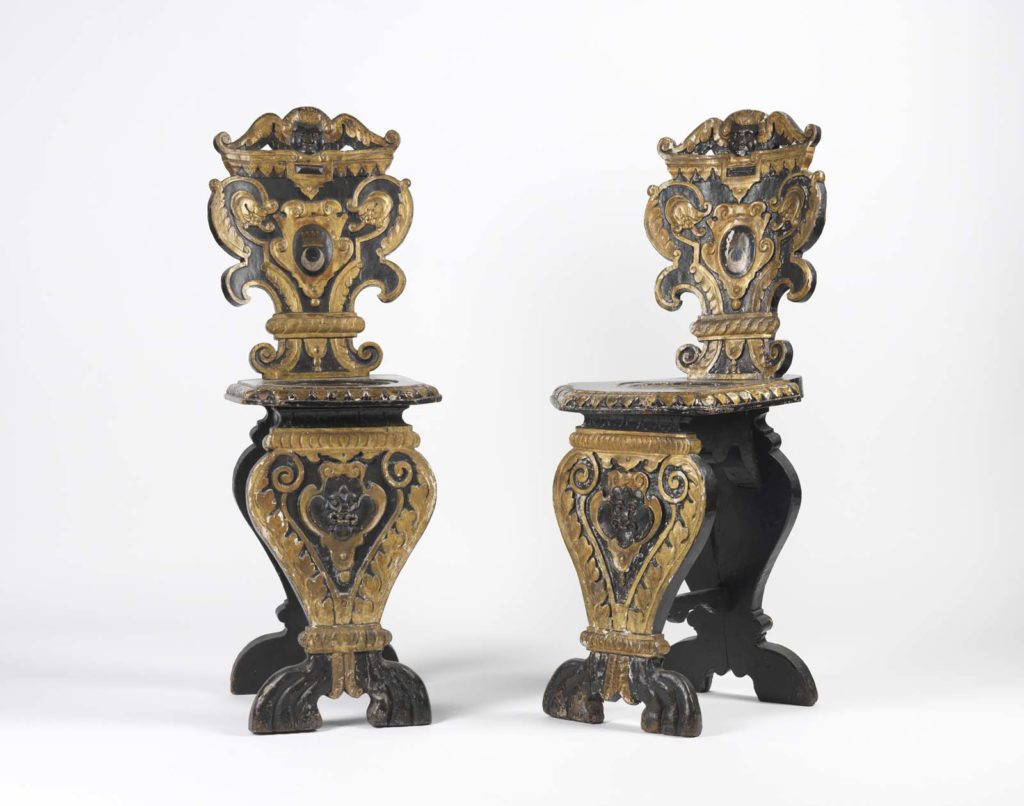 a photo of two matching wwooden carved chairs inlaid with gold leaf