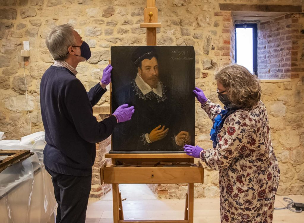 tow people looking at old paninting of a Tudor gentleman