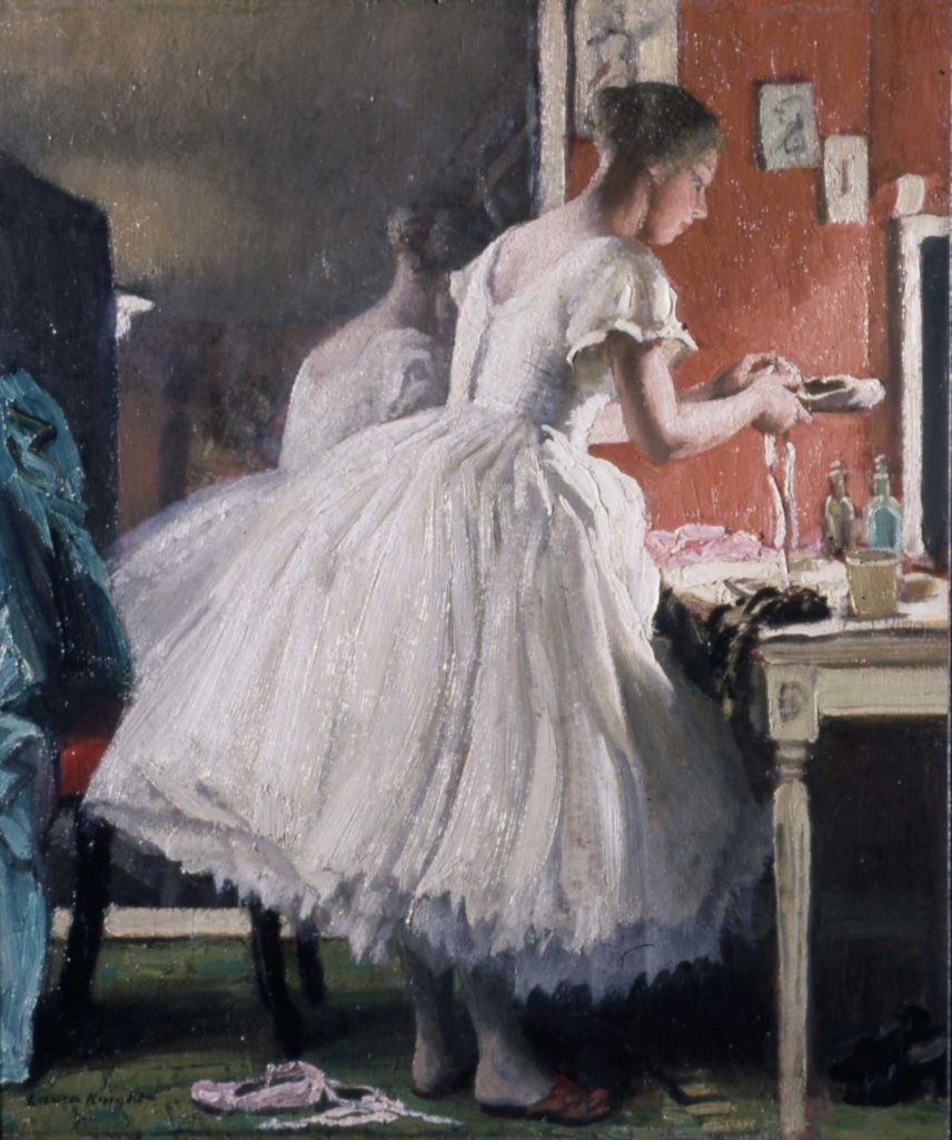 painting by Laura Knight shows a female ballet dancer in her dressing room in front of a mirror, which shows her back in the reflection. The overall colours of the painting are red, green and white and there is a strong and dramatic light on the dancer's face and upper body.