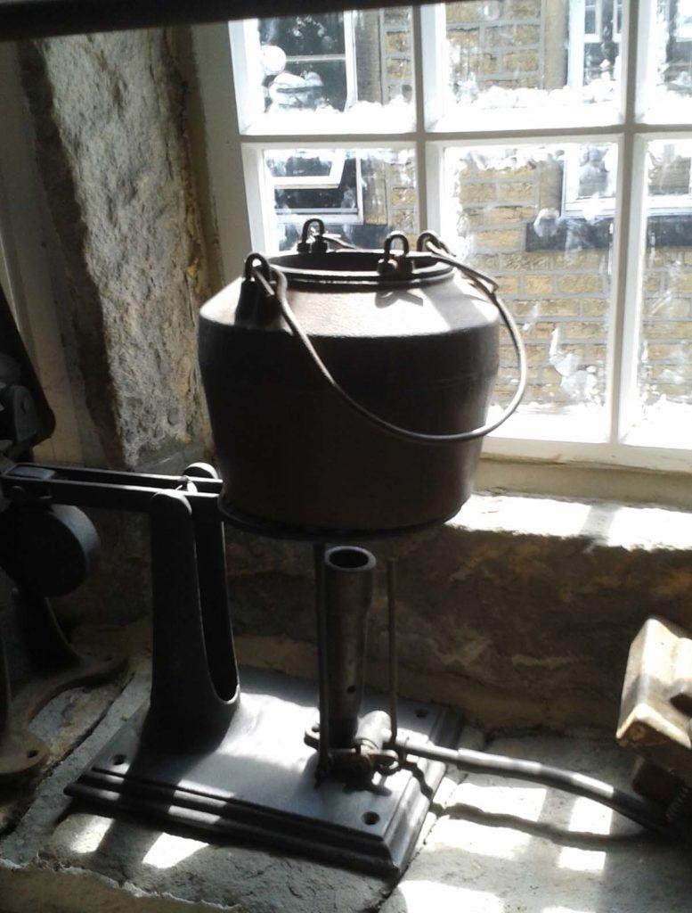 photo of a large iron kettle on a windowsill