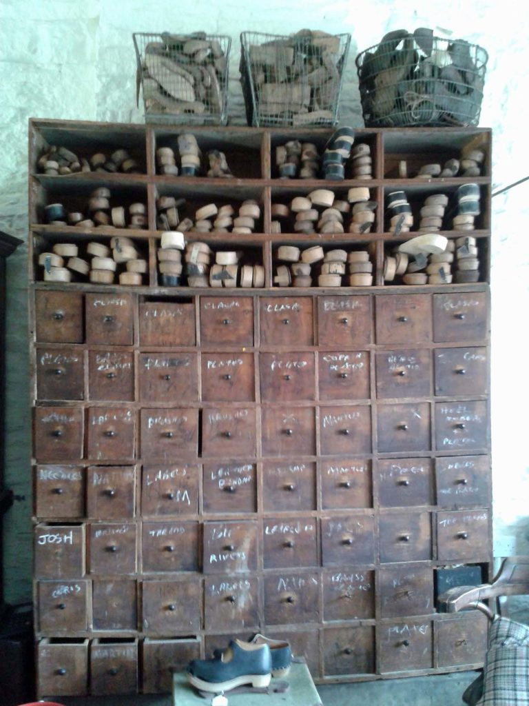 a photo of a series of old drawers with wooden clog soles stashed at the top