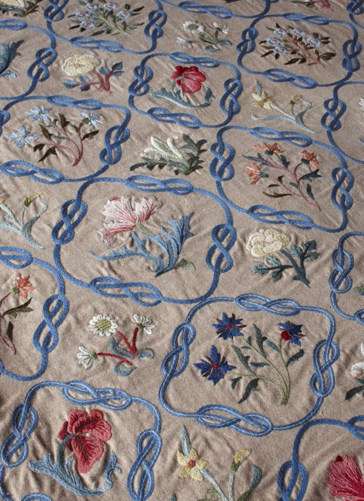 close up of a bed spreas with embroidered flowers