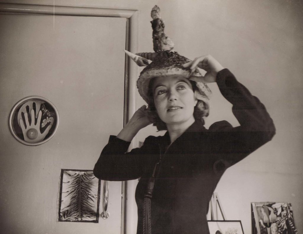 black and white photo of a woman wearing a hat with a stalagmite like protuberance emanating from the top