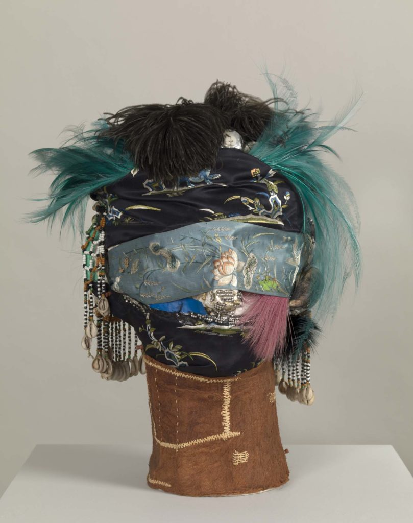 photo of a mask and hat made from feathers, scarves and other objects