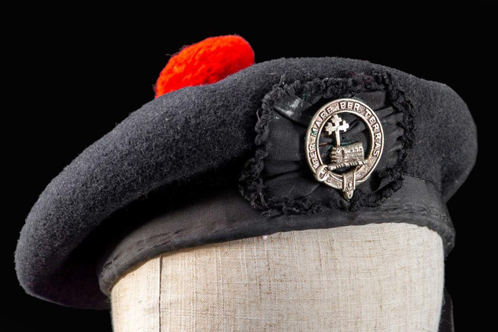 photo of a beret with red top bobble and cap badge