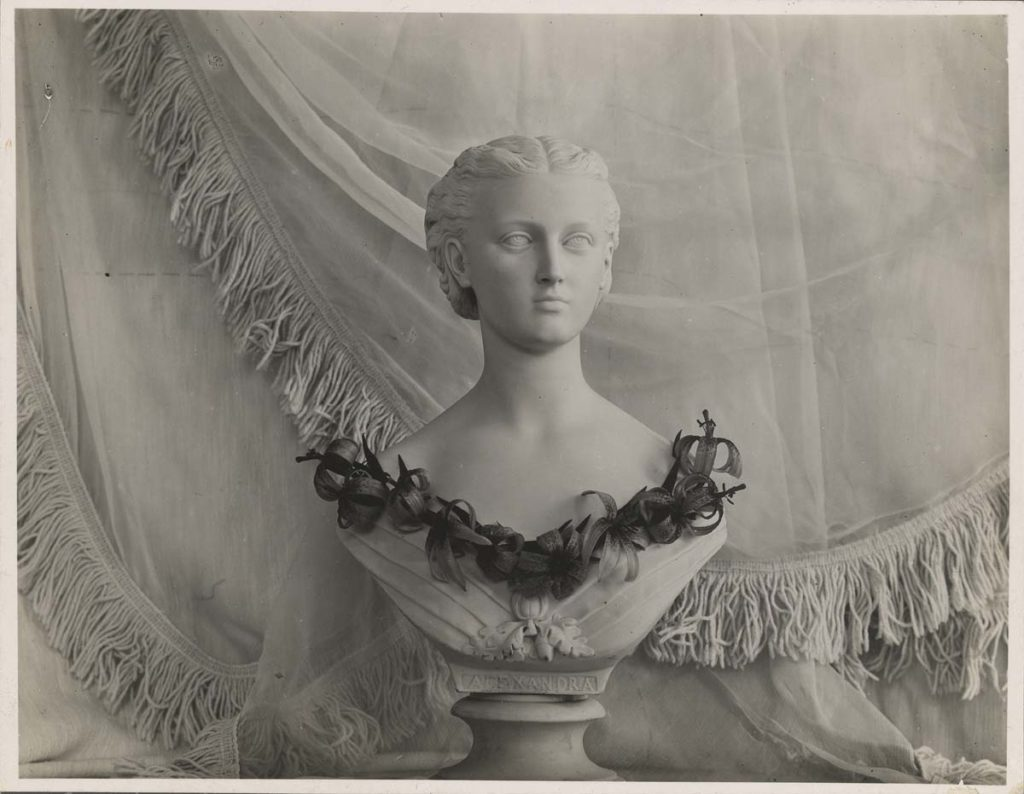 Photo of coronet and necklace of flowers on a sculpted bust of a woman