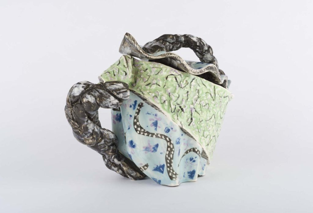 an abstract ceramic teapot with folded fabric like appearance