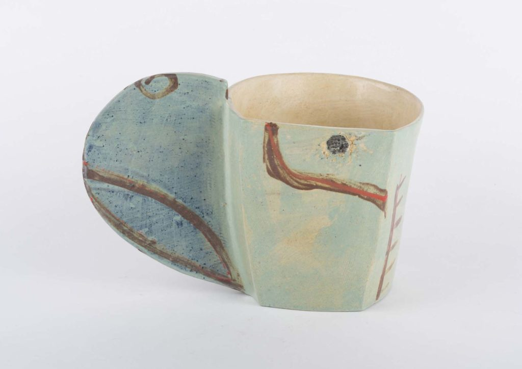 a cup with a large, solid, elliptical handle and light blue abstract decoration