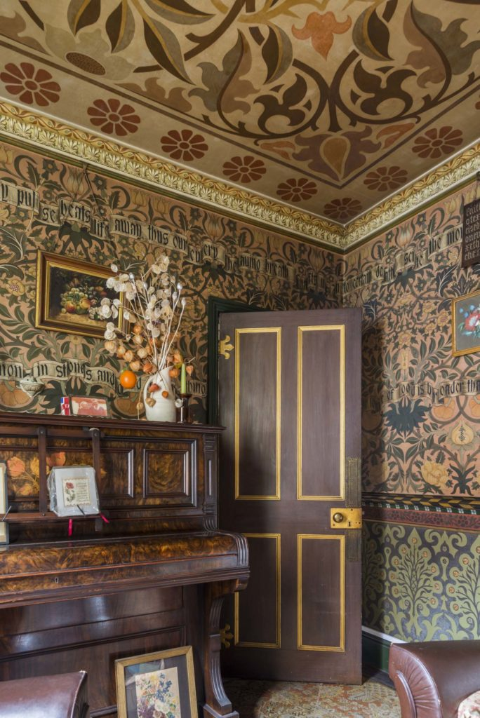 photo of a front room looking towards a brown and gold painted door next to a piano