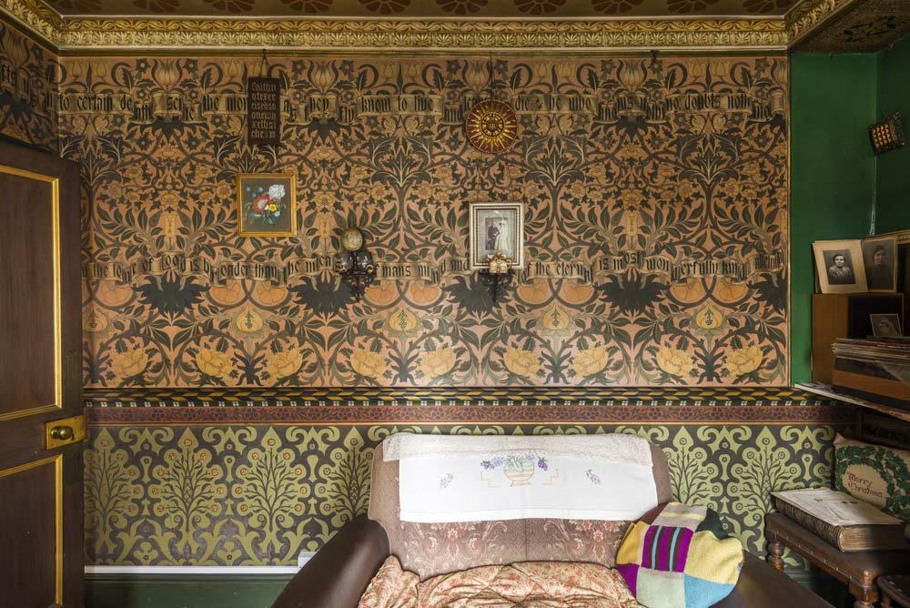 photo of a front wtih repeating pattern decorated wallpaper in greens, yellows and arts and crafts patternings