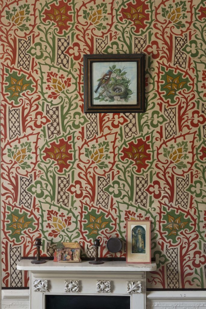 photo of repeating pattern wallpaper with a leaf motif in maroon and green above a fireplace