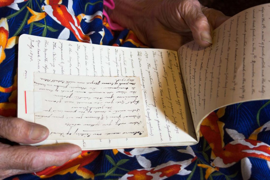 photo of two hands holding an open notebook with handwriting in it