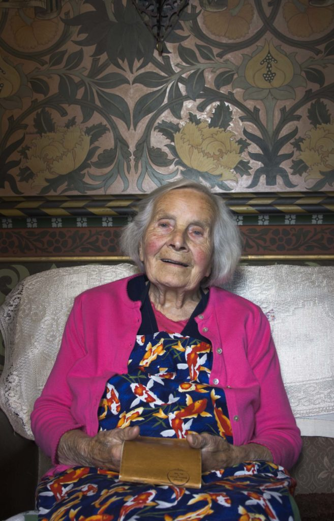 photo of a smiling elderly woman in a pink cardigan and floral dress holding an open notebook