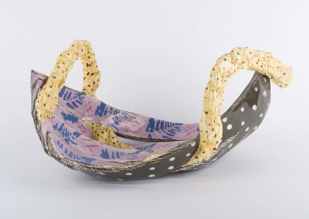 a curved flat ceramic dish with golden handles