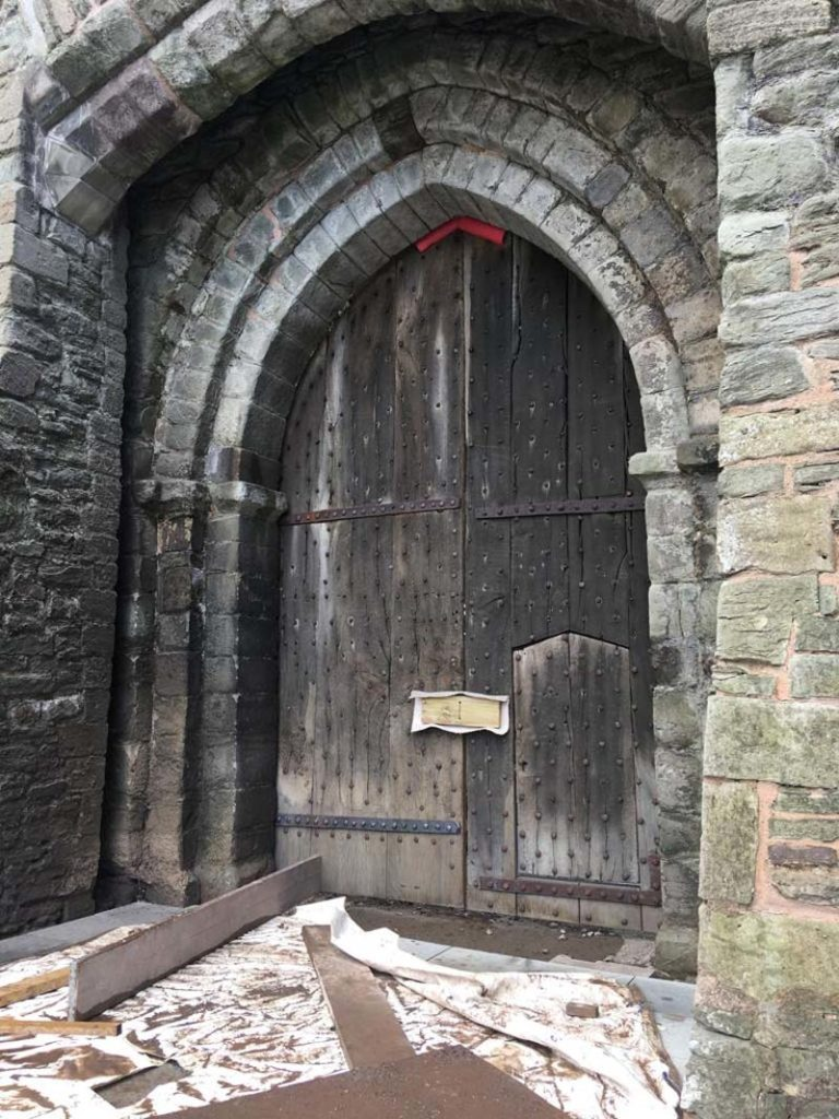 photo of a large wooden door in a castle's gothic archway