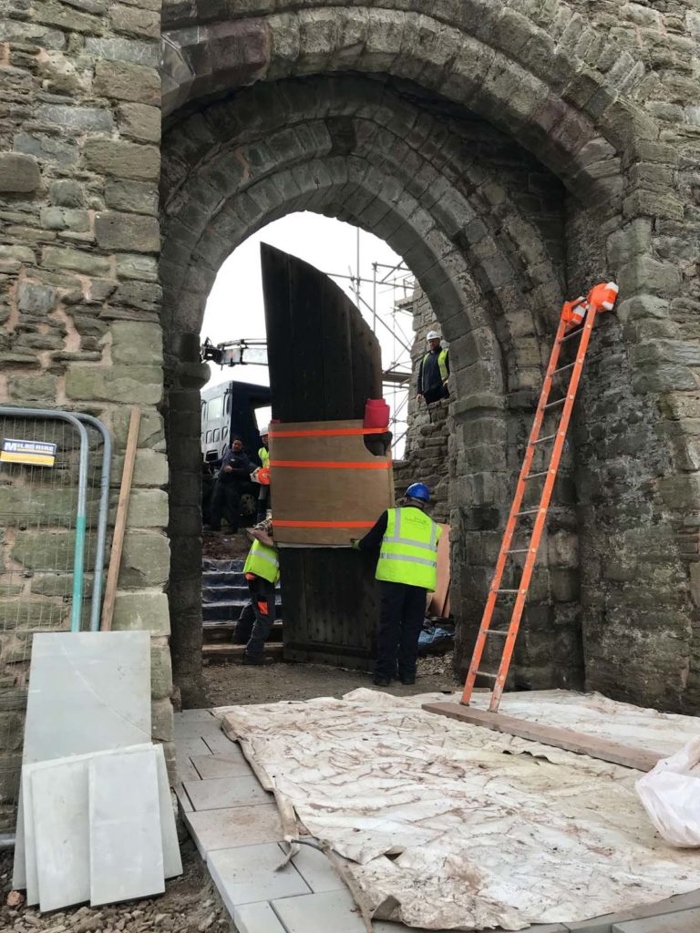 photo of a large wooden gate being manoeuvred into a stone doorway