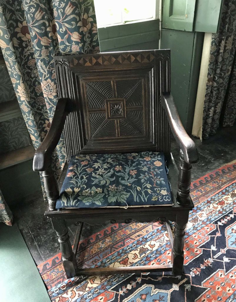 photo of a wooden armchair with Arts and Crafts style embroidered cushion