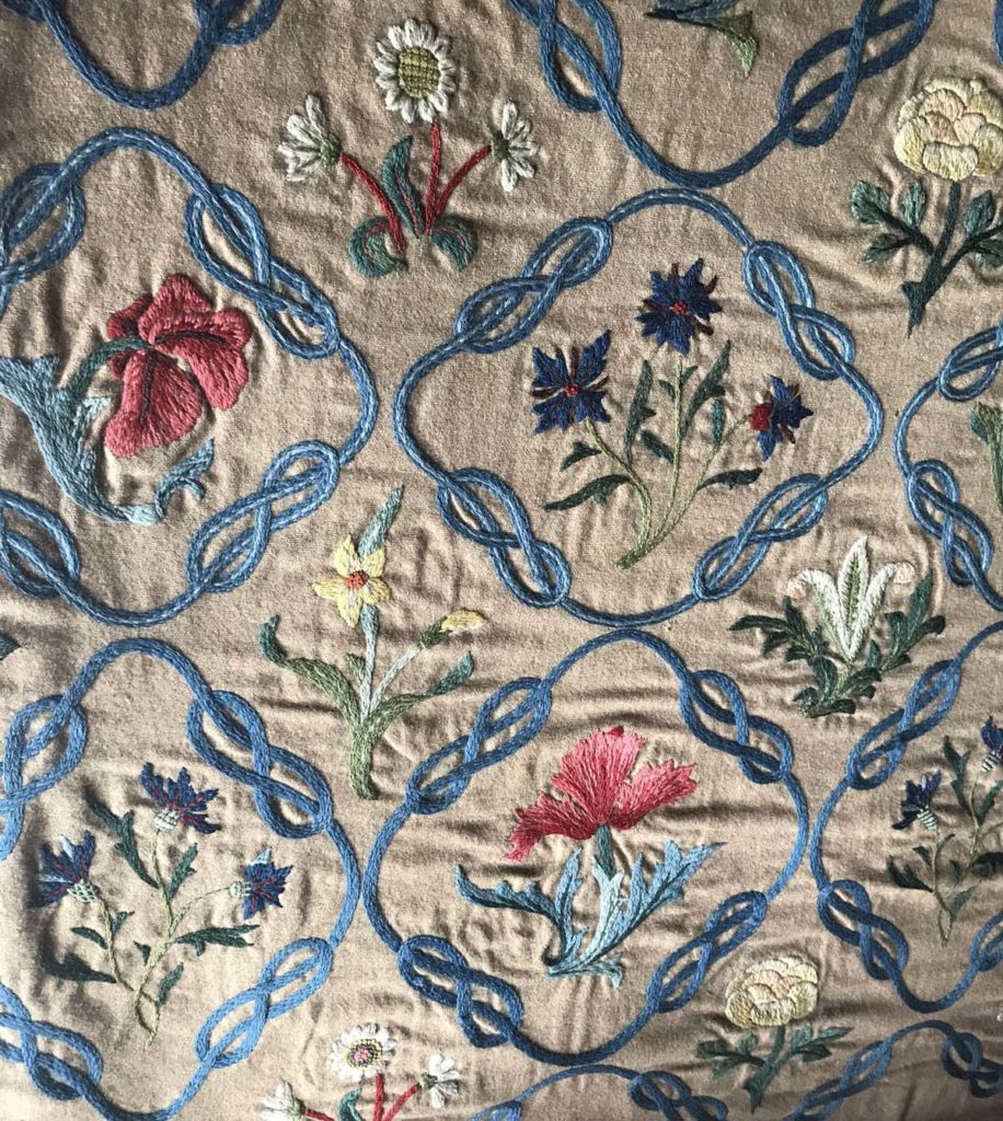 close up of an embroidered bedspread with flower designs