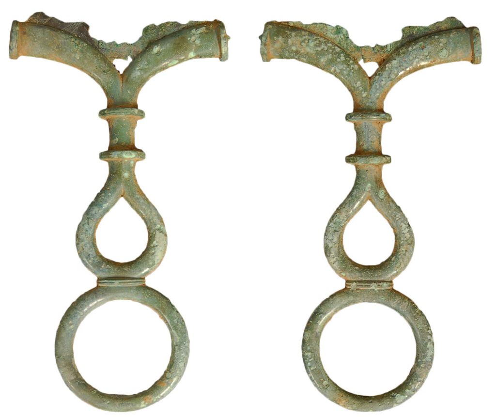 two ornate handles with circular features in worked bronze