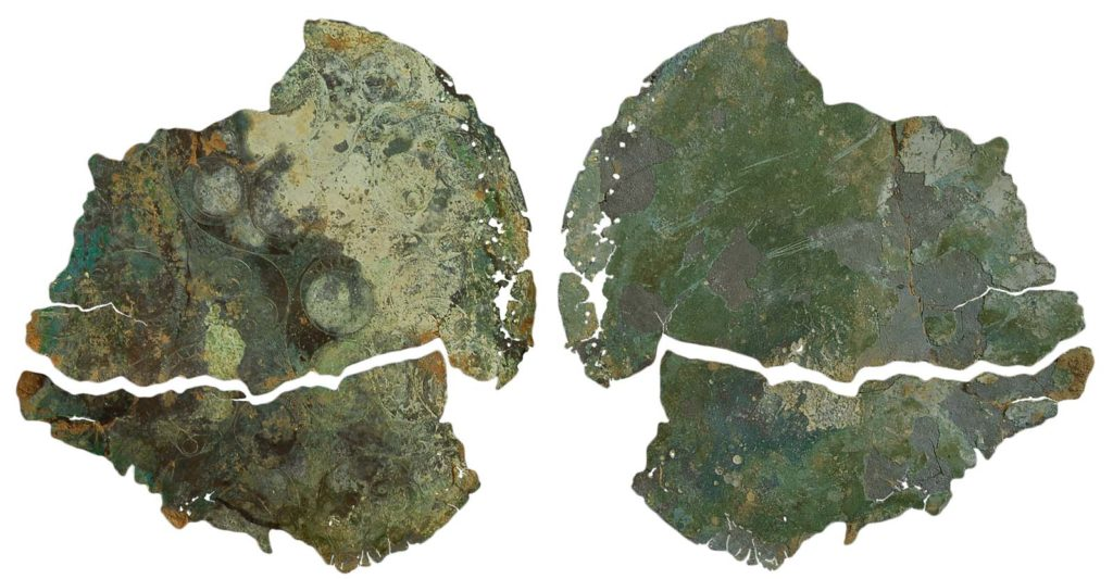 two disco like fragments made of corroded bronze