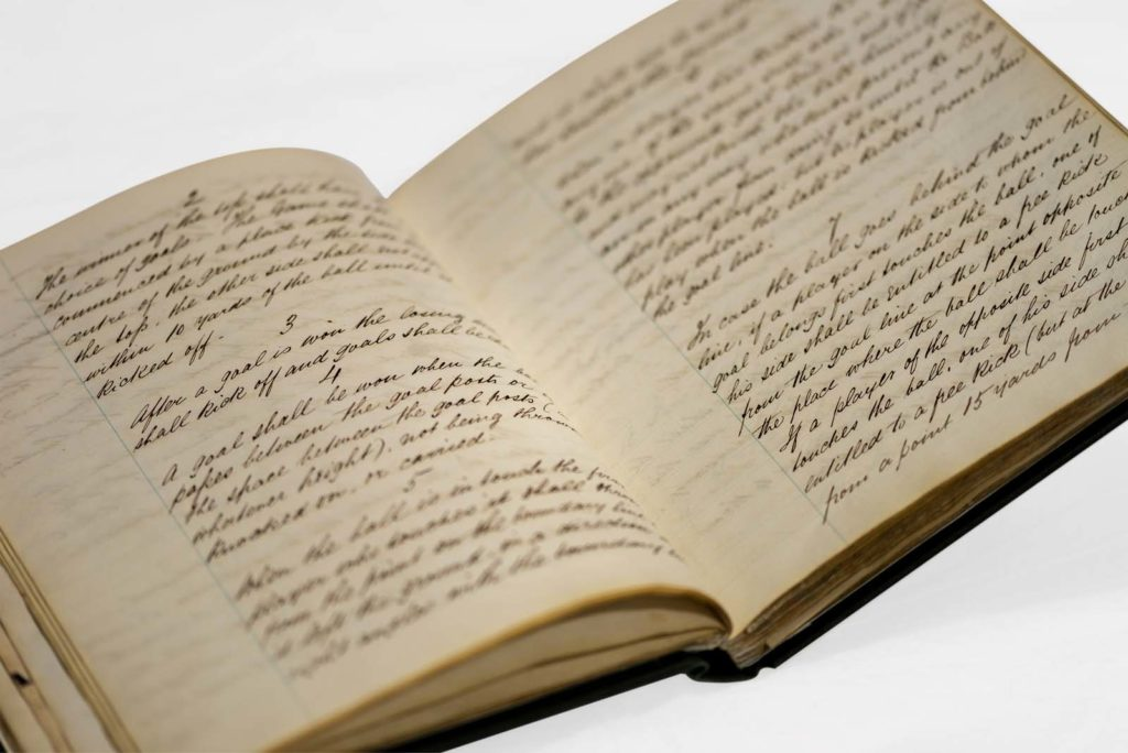an open book with neat handwritten textn in unfirom paragraphs talking about football rules