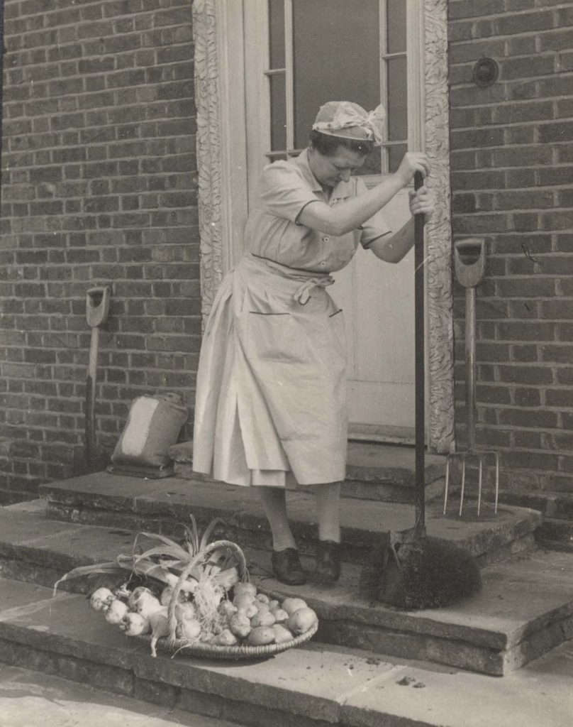 black and white photo of a woman in a headscarf scraping her shoes on the doorsteps of a house