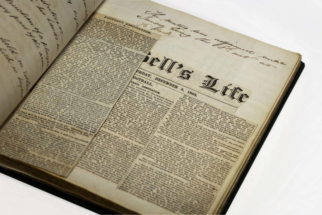 open journal with newspaper clippings about and hand-written text