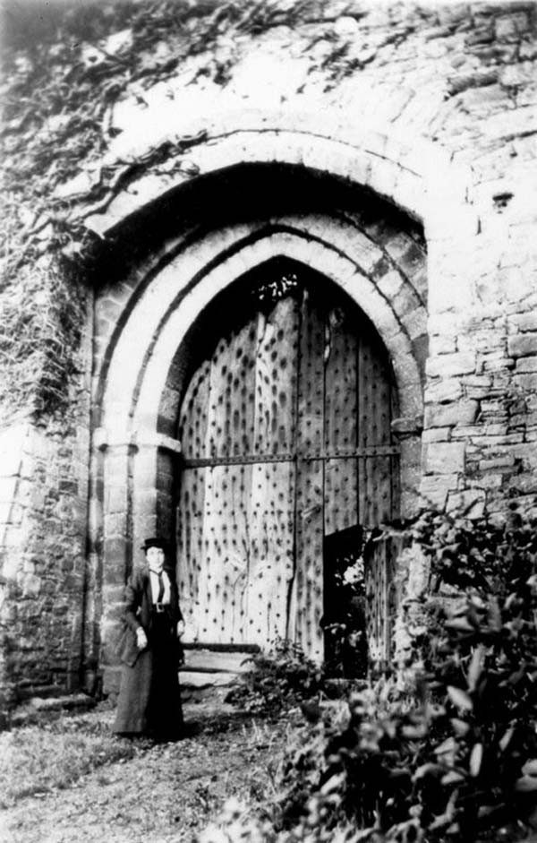 black and white photo of an Edwardian dressed woman standing next to a pair of wooden castle doors