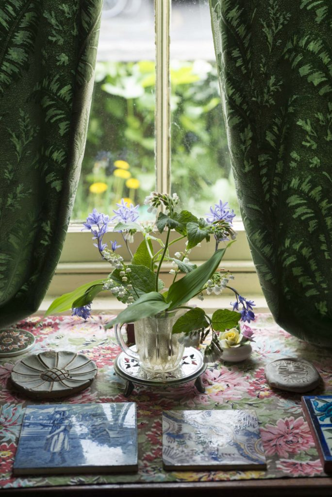 photo of an interior window with curtains and table set with vase flowers and crockery
