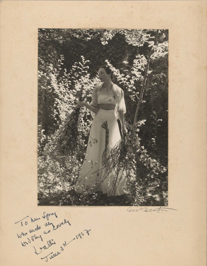 mounted photo of a woman in garden wearing a wedding dress and carrying flowers signed to the bottom left of the mount