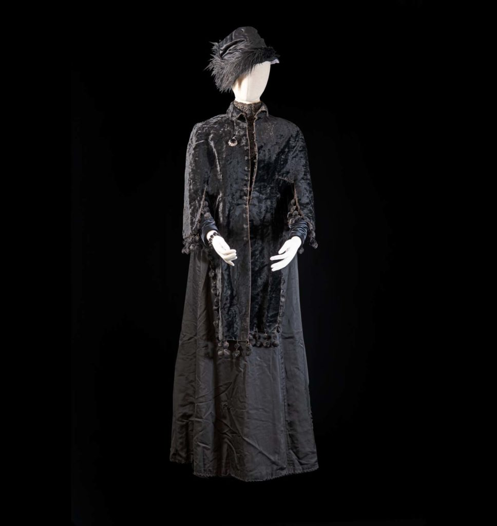 Long black Victorian dress with long sleeves and matching cap