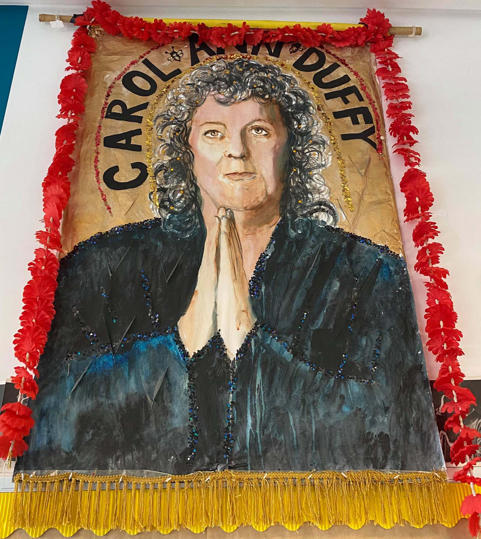 a banner with the central mage of a woman holding her hands as if in prayer