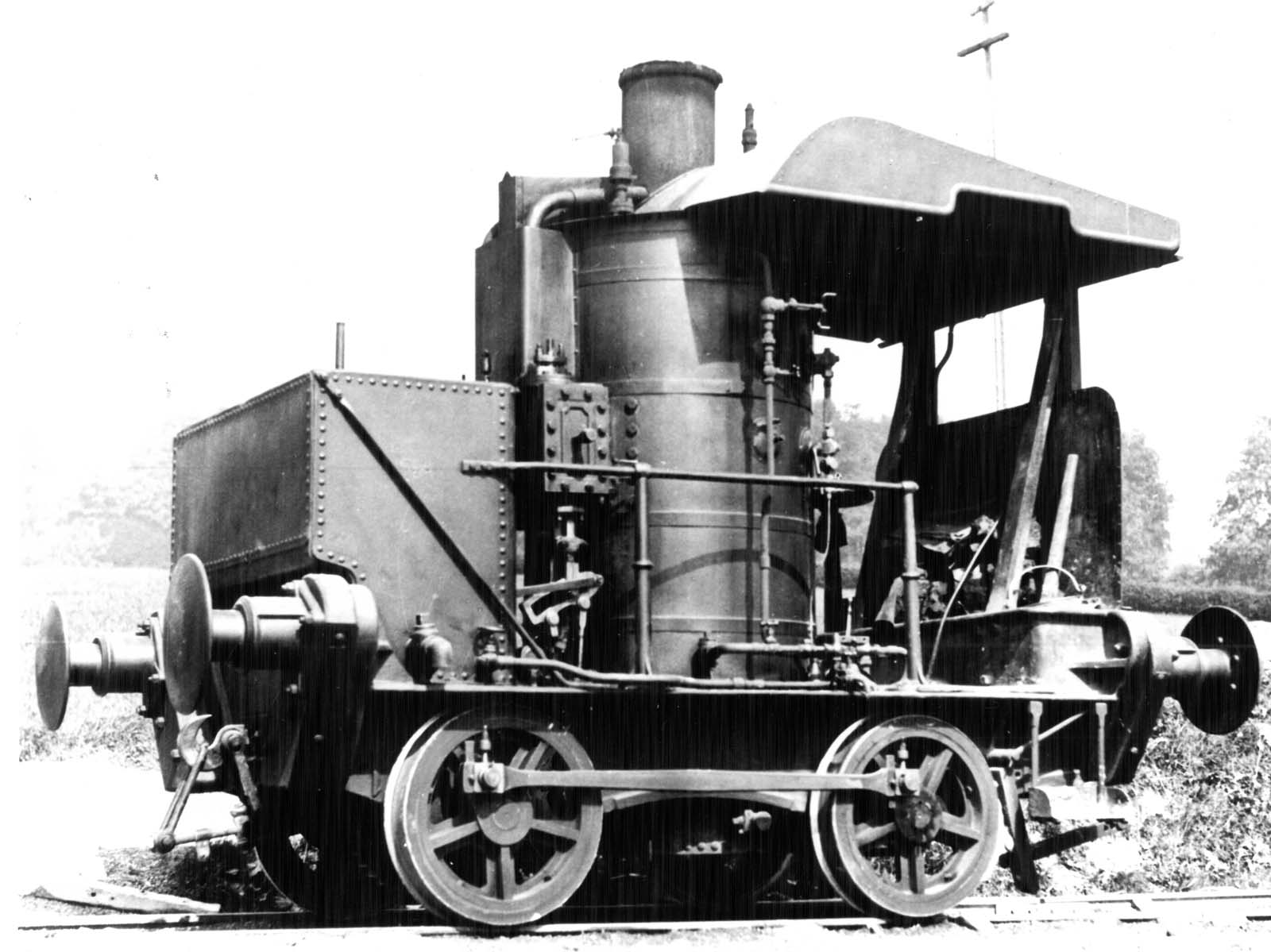 a black and white photo of a steam locomotive with large upright cylinder